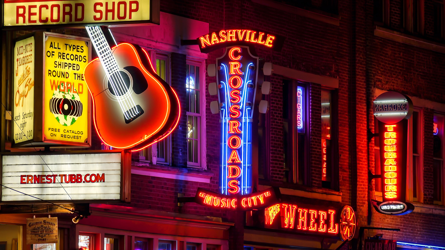 Neon signs at night along Broadway Street in Nashville, Tennessee.